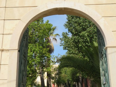 A view through one of the open gates leading into the palace grounds where extensive garden work is underway.