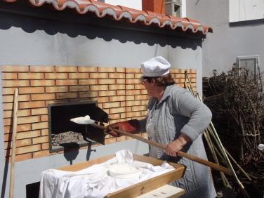 This woman was busily baking pao com chourico, chorizo stuffed bread.