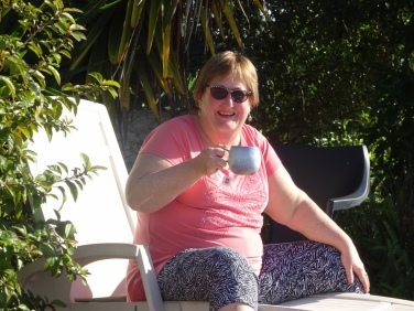 Patricia relaxing by the pool with a tea.